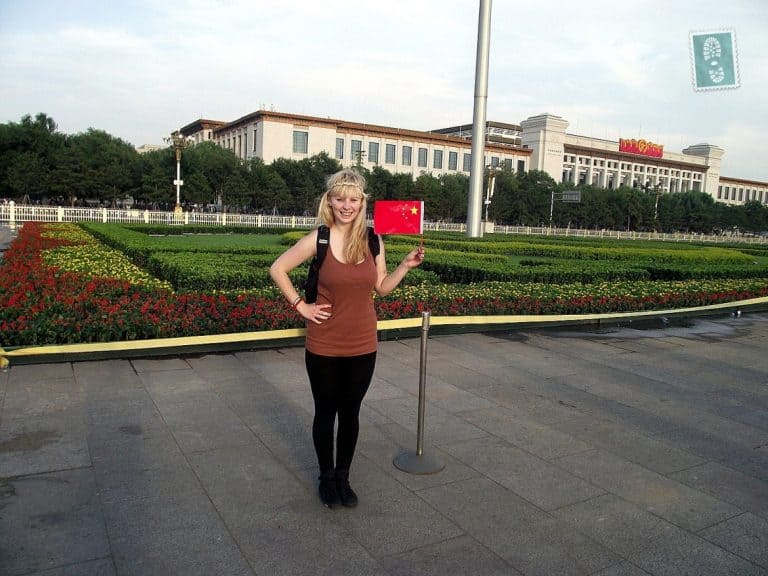 A girl standing on the square in Beijing holding a Chinese flag.