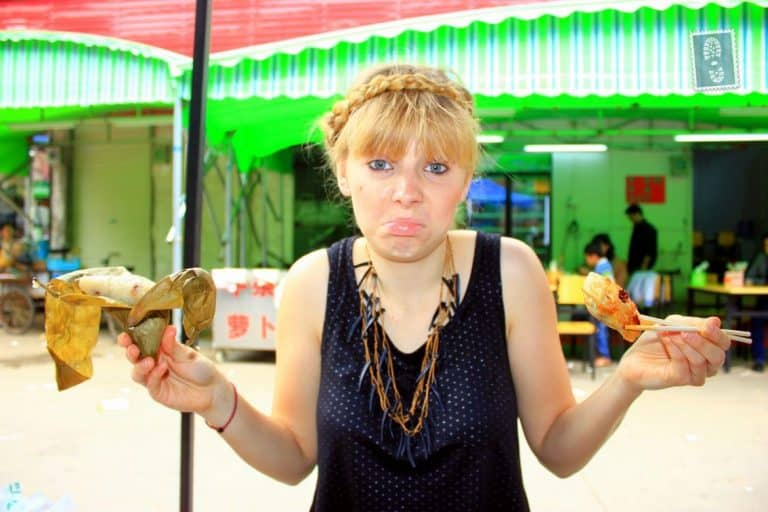 A girl is holding a sticky rice leaf and jiaozi in china