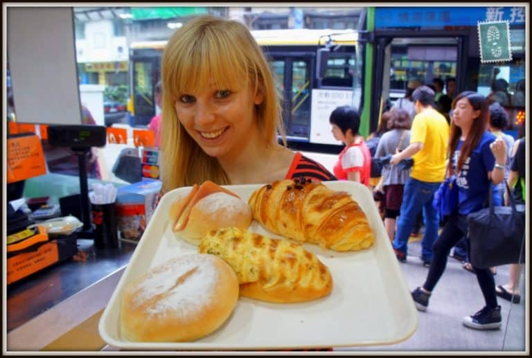 A girl is holding a tray with Chocolate croissant, had bun, garlic bread and mini cheese soft baguette in a bakery in Macau