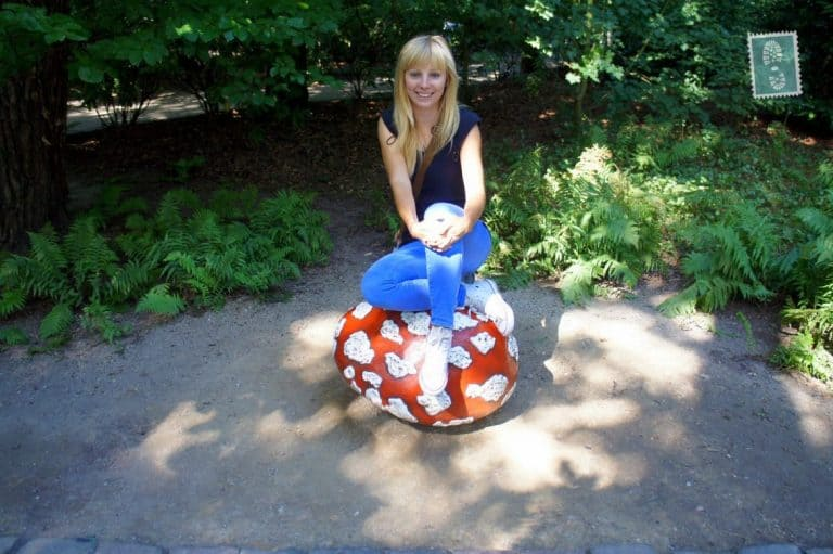 A girl sitting on one of the colorful mushrooms Efteling