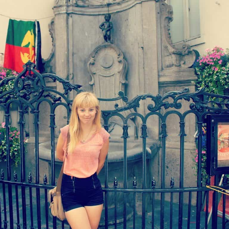 A girl standing in front of the Manneken Pis