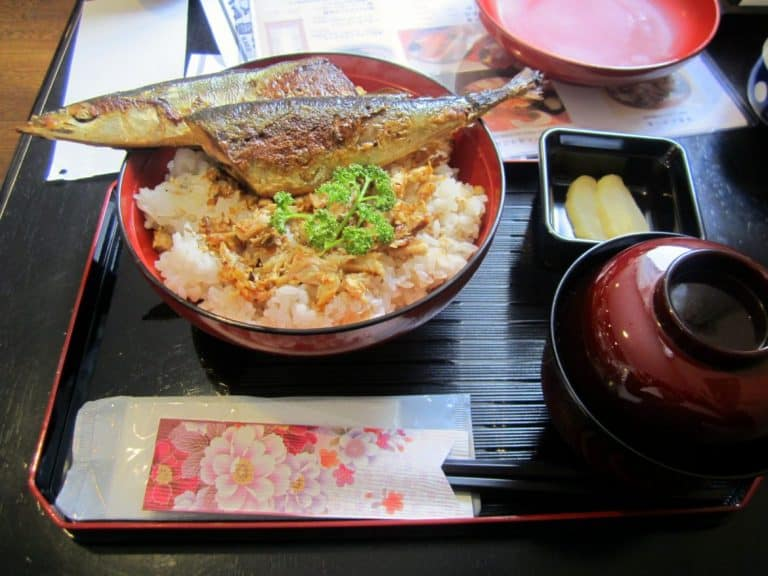 a bowl of miso soup, a bed of rice, fish, and pickled radishes.