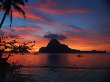 A red sunset over a limestone island in El Nido.
