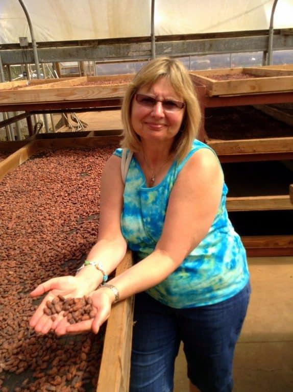 Doreen examining sun-dried cocoa beans in Hawaii