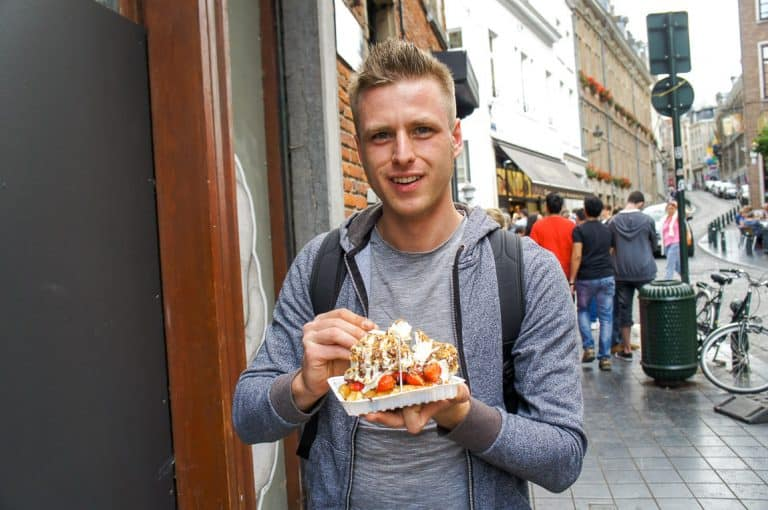 Cez of Etramping is eating a waffle in Brussels