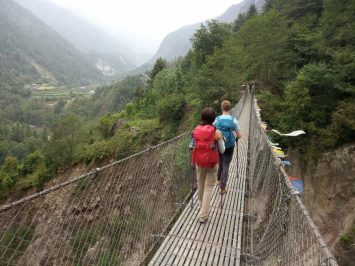 Lydia and Cez cross a chain bridge on the Everest Base Camp trek