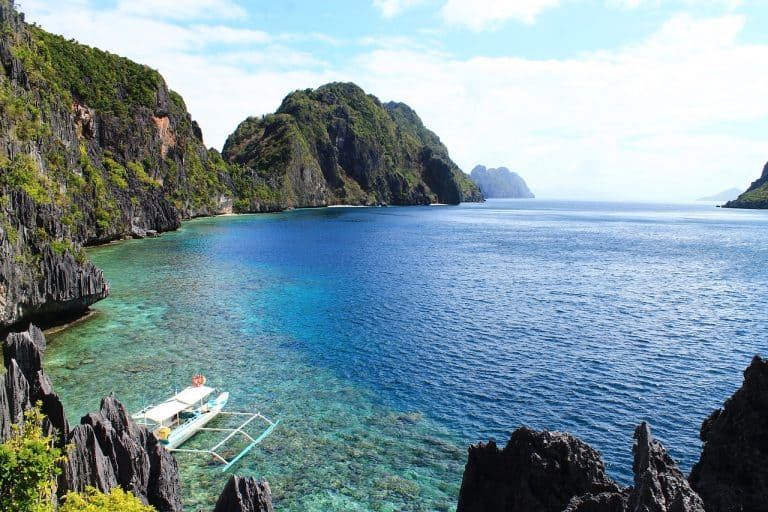 A bay surrounded by cliffs and a a local boat in El Nido.
