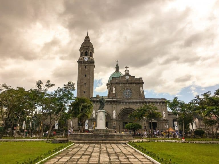 An Intramuros square with a statue and the cathedral in the background.