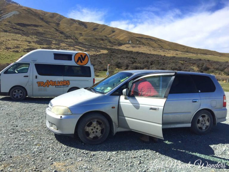 A rental campervan and a smaller camper car parked up at the side of a mountain.