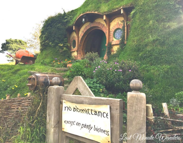 "A round door in the side of a grassy hill and a garden gate with a paper sign stating ""no admittance except on party business""."