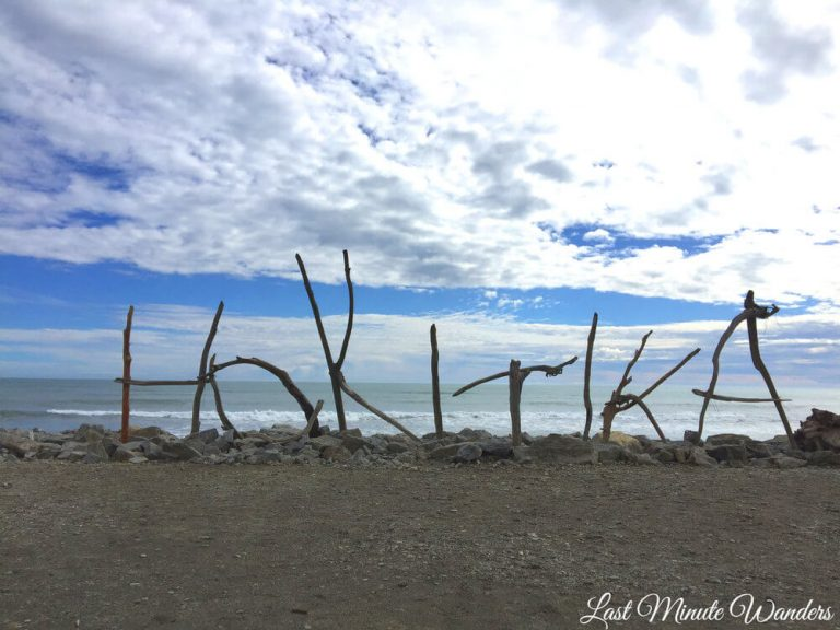 "View out to sea from beach with large driftwood letters spelling out ""Hokitika""."