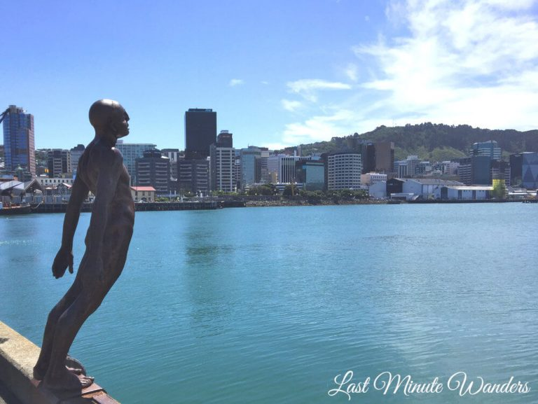 Statue of man leaning forward with arms behind him over the water and city buildings behind.