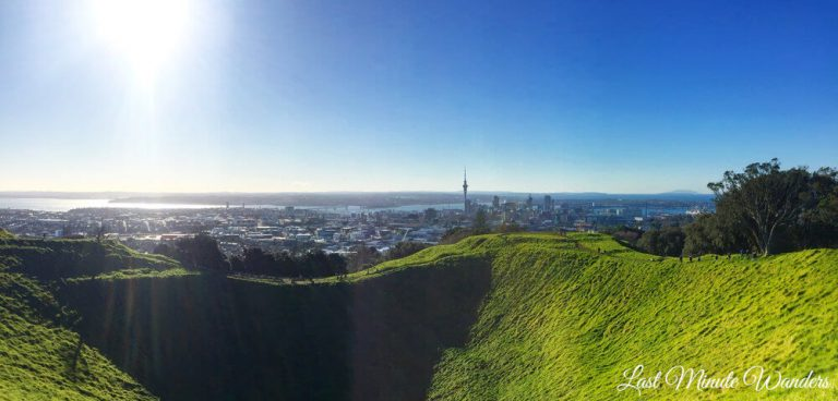 Grassy volcano crater in foreground with Auckland city in the background.